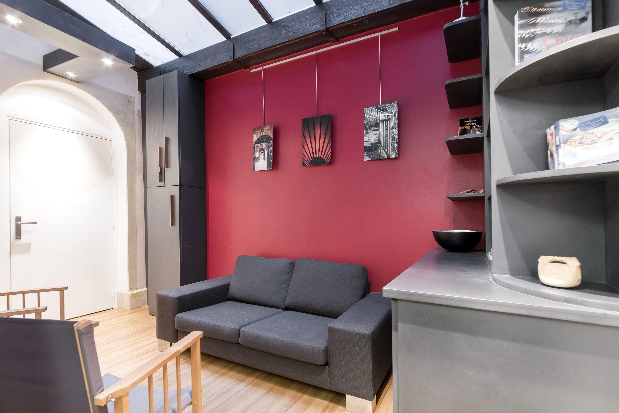 Un mur rouge chaleureux accompagne une bibliothèque et le canapé